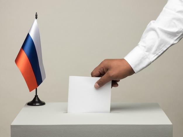 Urny z flagą narodową rosji. wybory prezydenckie w 2018 r. rzucanie kartą ręki