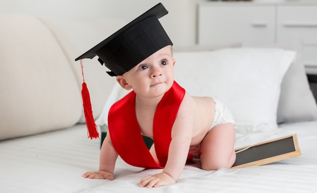 Urocza 10-miesięczna dziewczynka w czapce do ukończenia szkoły pełza po łóżku