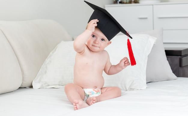 Urocza 10-miesięczna dziewczynka w czarnej czapce dyplomowej z frędzlami