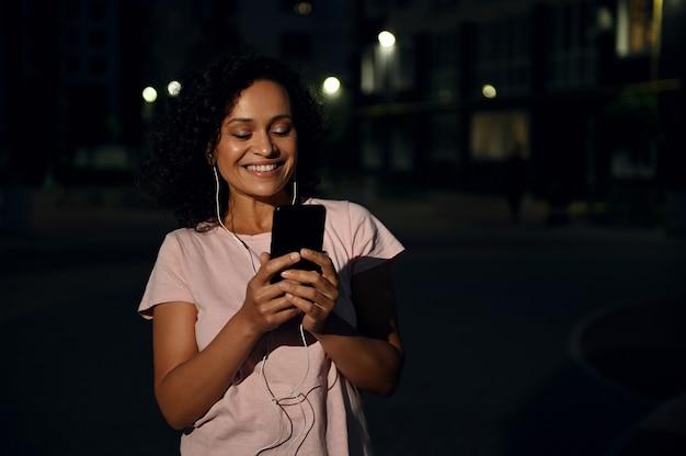 Urocza afroamerykanka ze słuchawkami w stroju sportowym, trzymająca telefon komórkowy i uśmiechająca się z uśmiechem na ustach