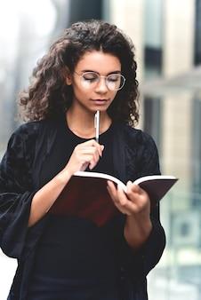 Urocza afroamerykańska piękna szczęśliwa kobieta robiąca notatki w notatniku podczas spaceru na świeżym powietrzu po mieście