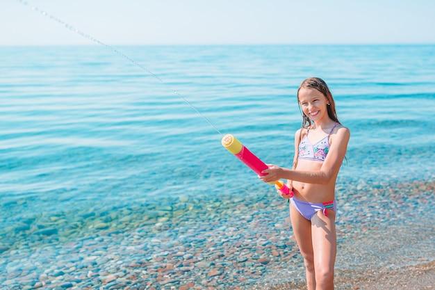 Urocza aktywna dziewczynka na plaży podczas letnich wakacji