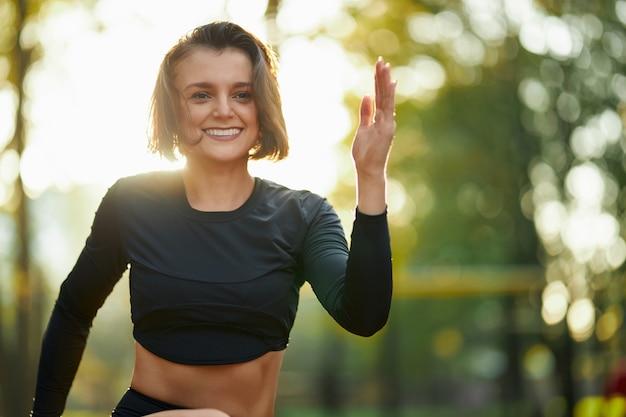 Urocza aktywna kobieta uprawiająca aktywność fizyczną w parku miejskim