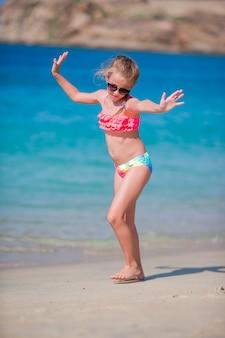 Urocza aktywna mała dziewczynka na plaży podczas wakacji