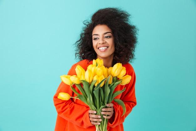 Urocza amerykanka w czerwonej koszuli, patrząc na bok i trzymając bukiet pięknych żółtych tulipanów, odizolowanych na niebieskiej ścianie