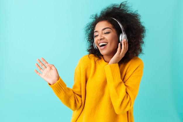 Urocza amerykanka w żółtej koszuli śpiewa i bawi się podczas słuchania muzyki za pomocą bezprzewodowych słuchawek, odizolowane na niebieskiej ścianie