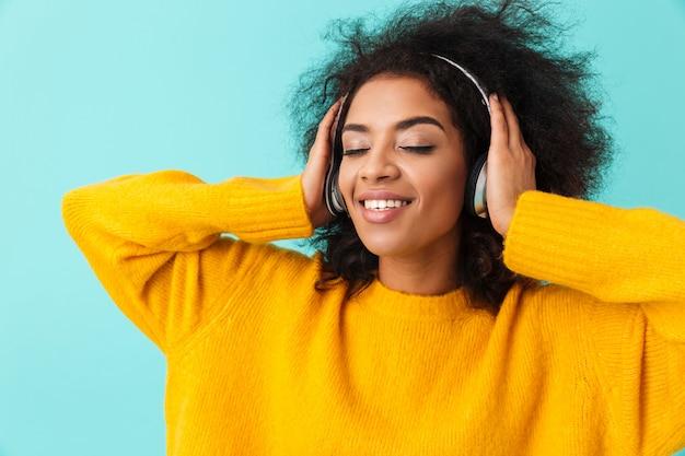 Urocza amerykańska uśmiechnięta kobieta w żółtej koszuli, słuchanie muzyki za pomocą bezprzewodowych słuchawek, odizolowane na niebieskiej ścianie