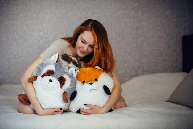 Urocza atrakcyjna kobieta przytula swoje dziecięce zabawki.