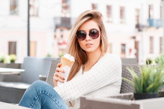 Urocza atrakcyjna młoda hipster kobieta w vintage stylowy sweter w modnych niebieskich dżinsach w modnych okularach przeciwsłonecznych z lodami w dłoniach siedzi w ulicznej kawiarni. śliczna dziewczyna.
