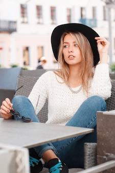 Urocza atrakcyjna młoda kobieta w białym swetrze vintage w stylowych dżinsach w trampkach w czarnym eleganckim kapeluszu siedzi na sofie przy szarym stoliku w ulicznej kawiarni w ciepły wiosenny dzień. śliczna dziewczyna.