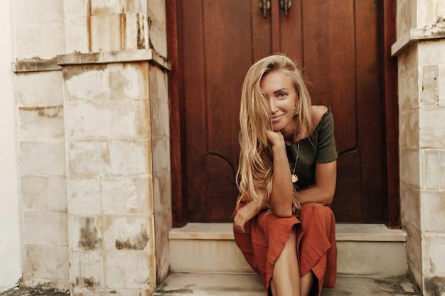 Urocza atrakcyjna młoda opalona blondynka w krótkiej bluzce w kolorze khaki i czerwonych luźnych spodniach uśmiecha się szczerze i siedzi na schodach w pobliżu drewnianych drzwi