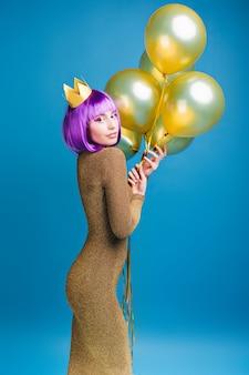 Urocza atrakcyjna modna młoda kobieta w luksusowej sukience ze złotymi balonami. strzyżone fioletowe włosy, korona na głowie, wesołe emocje, świętowanie.
