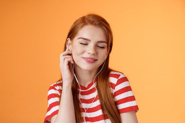 Urocza atrakcyjna ruda kaukaska kobieta słucha muzyki zamknij oczy delikatny uśmiech dotknij słuchawki ucho ...