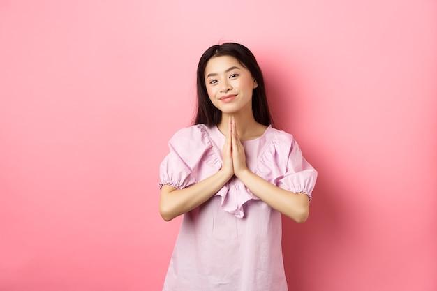 Urocza azjatka dziękuje, uśmiecha się i wygląda na zadowoloną, pokazując gest namaste z wdzięcznością, stojąc w sukience na różowym tle.
