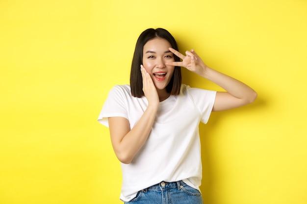 Urocza azjatka w białej koszulce pozuje z ręką na policzku, pokazuje znak pokoju na oku, stojąc nad żółtym.