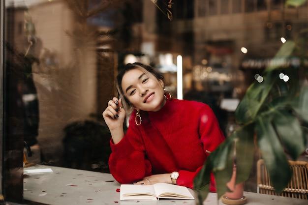 Urocza azjatka w czerwonym stroju z dzianiny i masywnych kolczykach uśmiecha się siedząc w kawiarni z notatnikiem na stole