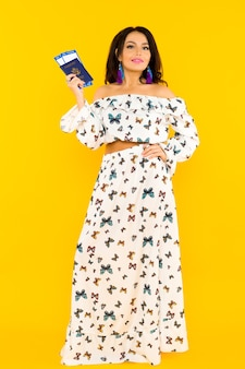 Urocza azjatka w jedwabnej sukience z motylami trzyma paszport i bilety lotnicze