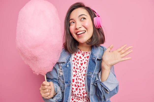 Urocza azjatka z marzycielskim wyrazem unosi dłoń trzymającą pyszną watę cukrową słucha ścieżki dźwiękowej ubranej w modne ubrania odizolowane na różowej ścianie. koncepcja zabawy rekreacyjnej dla ludzi