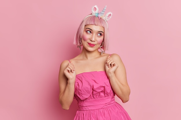 Urocza azjatka z różowymi włosami skoncentrowanymi na boku ma rozmarzoną twarz unoszącą ręce