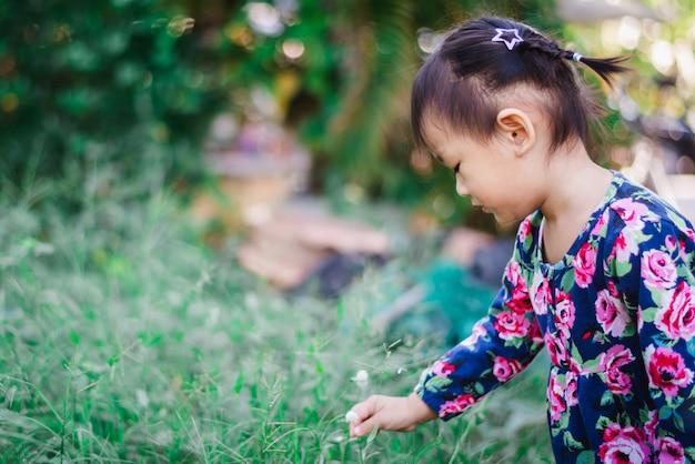 Urocza azjatycka dziewczyna cieszy się z trawą i kwiatem w ogrodowy plenerowym