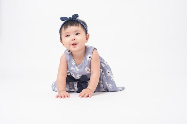 Urocza azjatycka dziewczynka jest portretem na biel ścianie