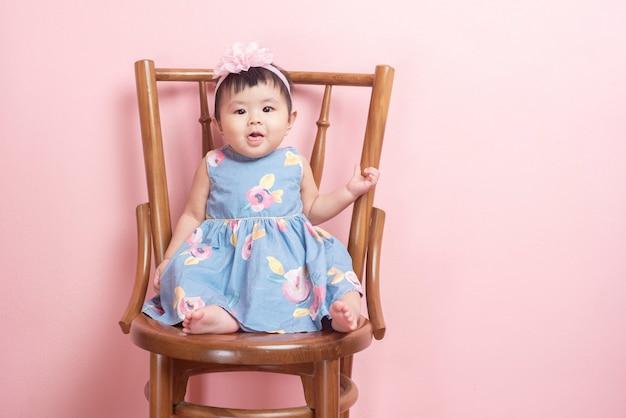 Urocza azjatycka dziewczynka jest portretem na menchii ścianie
