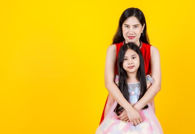 Urocza azjatycka matka pielęgnuje młodą uroczą córkę jako ukochaną, uprzejmie przytulając się od tyłu z ciepłą rodzinną miłością i empatią, opieką nad dziewczynką, razem uśmiechając się do izolowanego portretu szczęśliwej pary żeńskiej
