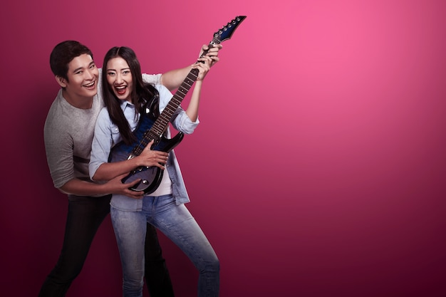 Urocza azjatykcia para bawić się gitarę