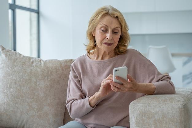 Urocza babcia siedząca na kanapie w salonie domu robiąca zakupy online