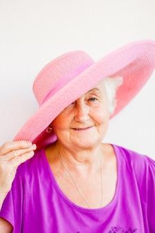 Urocza babcia w różowym kapeluszu z niebieskimi oczami i delikatnym uśmiechem