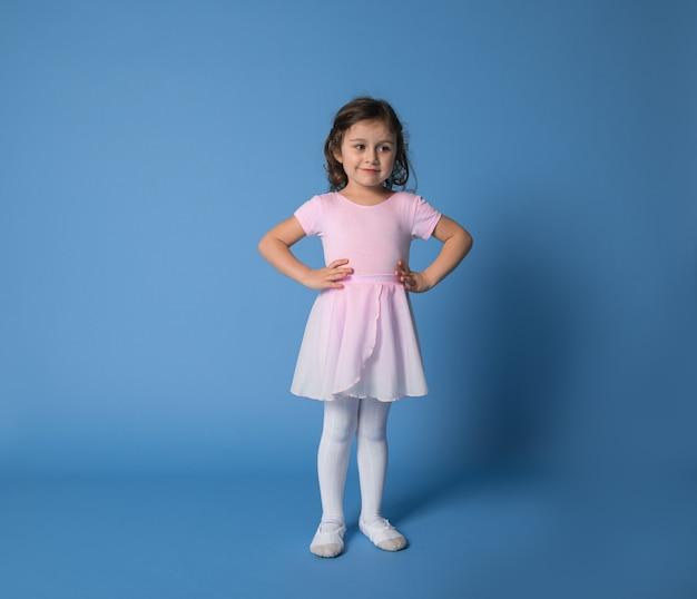 Urocza baletnica ubrana w różowy mundur pozuje do aparatu z rękami w pasie