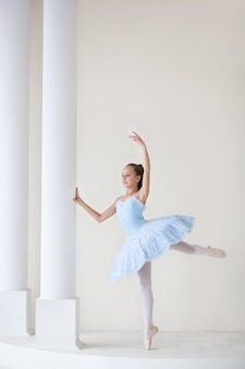 Urocza baletnica w stroju baletowym i pointe tańczy. dziewczyna w klasie tańca. dziewczyna uczy się baletu. balerina tańczy. piękna tancerka ćwiczy przy lustrze.