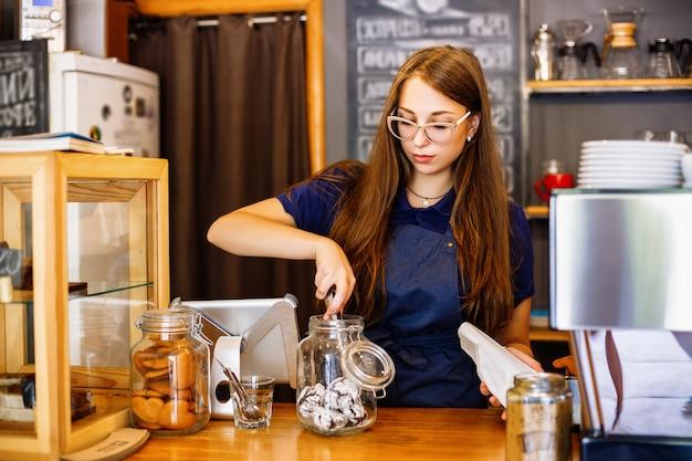 Urocza barista składa piernik w paczce w kawiarni