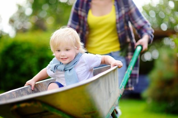 Urocza berbeć chłopiec ma zabawę w wheelbarrow pcha mamą w domowym ogródzie na ciepłym słonecznym dniu. aktywne gry na świeżym powietrzu dla dzieci w lecie.