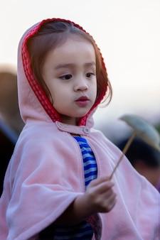 Urocza berbeć dziewczyna ma zabawę na zima dniu. dzieci bawią się na zewnątrz. moda zimowa dla dzieci.