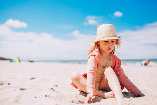 Urocza berbeć dziewczyna w kapeluszu bawić się na białej piasek plaży przy plażą. letnie wakacje.