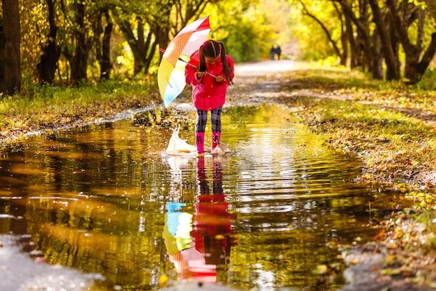 Urocza berbeć dziewczyna z kolorowym parasolem outdoors przy jesień deszczowym dniem