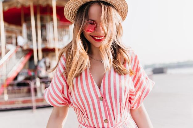 Urocza biała dziewczyna w słomkowym kapeluszu śmiejąc się na rozmycie miasta. dość europejska młoda dama w pasiastej sukience, zabawy w parku rozrywki.
