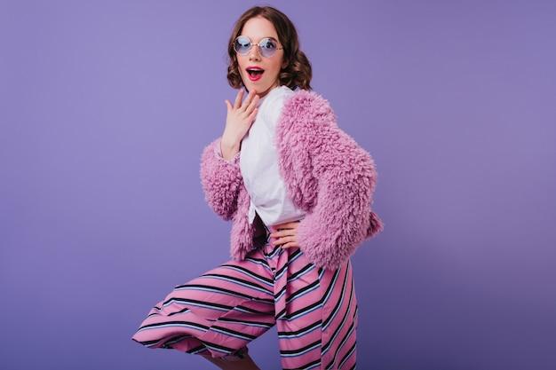 Urocza biała kobieta w okularach przeciwsłonecznych z zaskoczonym wyrazem twarzy na fioletowej ścianie. kryty ujęcie zdumionej czarującej dziewczyny w różowych spodniach i futrzanej kurtce.