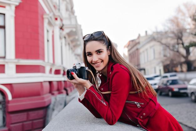 Urocza biała kobieta w stylowym czerwonym stroju robienia zdjęć z widokiem na ulicę