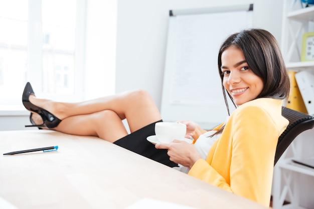 Urocza bizneswoman odpoczywająca z kawą w biurze i patrząca na przód