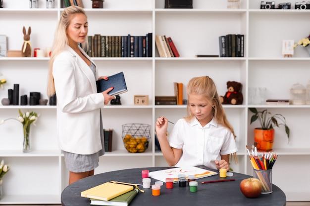 Urocza, blond dziewczyna rysuje obrazek z sercami. matka czule patrzy na córkę