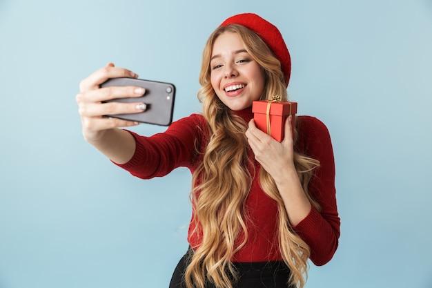 Urocza blond kobieta lat 20. trzymając pudełko urodzinowe podczas robienia zdjęcia selfie na telefon komórkowy na białym tle