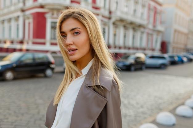 Urocza blond kobieta w jesiennym modnym stroju spacerującym po mieście