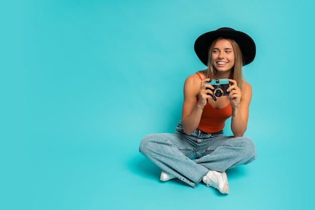 Urocza blond kobieta w stylowym letnim stroju trzyma aparat retro, siedząc na podłodze w studio na niebieskiej ścianie. wakacyjny nastrój.