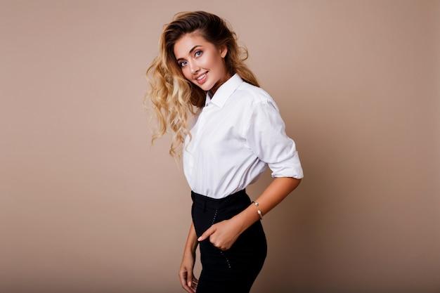 Urocza blond kobieta z idealnym uśmiechem w białej bluzce pozuje na beżowej ścianie. stylowy strój roboczy.