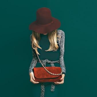 Urocza blond modelka w modnej czerwonej czapce i czerwonej kopertówce na zielonym tle