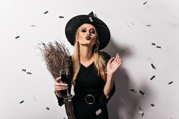 Urocza blond wiedźma delektująca się winem. wesoła jasnowłosa dama w kostiumie maskarady pozuje na imprezie z okazji halloween.