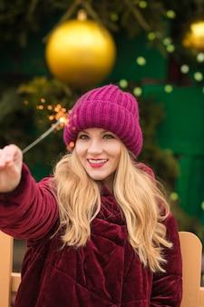 Urocza blondynka bawi się błyszczącymi światłami bengalskimi na noworocznym świerku w kijowie