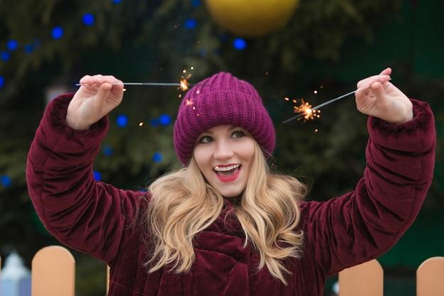 Urocza blondynka bawi się lśniącymi światłami bengalskimi na noworocznym świerku w kijowie